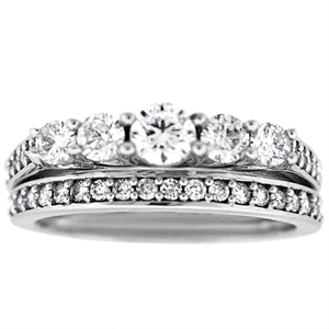 This unique and beautiful white gold diamond bridal set with engagement ring and wedding ring has shinning 1.0 carat diamonds. Engagement ring has five, tapered in size, round diamonds and round diamonds on the shank and band.  Bridal set has diamond carat total weight of 1.0 carats including the wedding band.  Diamond bridal duo is set in 14 karat white gold setting.