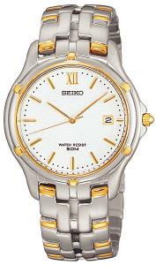 Sporty yet stylishly contemporary, the two-tone stainless steel men's watch is the perfect complement to today's business and casual wear. The round watch case measures 1.55 inches in diameter and it features a slightly raised bezel with a gold-tone ring and gold-tone studded accents. The white dial background hosts thin, gold stick dial markers, thin gold-tone hands (with second hand), a date function at 3 o'clock, and small minute indexes that surround the outer dial. The silver stainless steel bracelet band features trident-shaped links with polished gold-tone accents. Other features include Japanese quartz movement, a scratch-resistant sapphire crystal, and water resistance to 50 meters (165 feet).